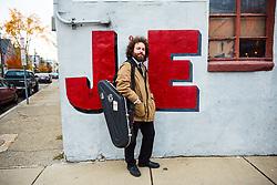 Man Standing on Street Corner Carrying Instrument Case