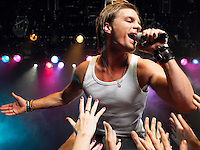 Young Man Singing on stage in concert close to adoring fans low angle view
