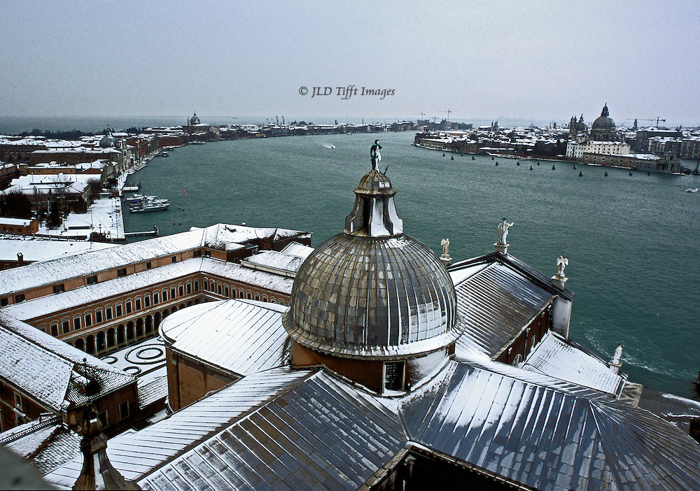 Venice under snow seen from the campanile of the Palladian church of San Giorgio Maggiore.. Church dome, roof, and monastery in foreground; laguna beyond with Giudecca on the left and San Marco district on the right.