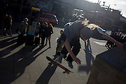Commuters watch a young skateboarder flying through the air during his acrobatic jump over steps during London's rush hour.