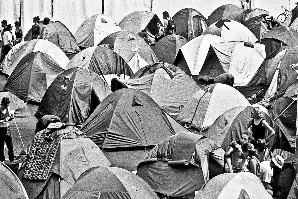 Genova, venerdì 20 luglio 2001. Giornata delle piazze tematiche. Prima del corteo della disobbedienza civile, un manifestante si prepara alla giornata indossando protezioni rigide, tra le tende dello stadio Carlini.