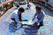 """NINGBO, CHINA - OCTOBER 14: (CHINA OUT) <br /> <br /> Nearly a Thousand of License Plates Wait for owners<br /> <br /> Policemen check the unclaimed license tags outside Jiangdong Traffic Police Brigade\'s office on October 14, 2013 in Ningbo, Zhejiang Province of China. Typhoon """"Fitow"""" brings the city water-logging and let many wading missing license plates, the final account of unclaimed license tags are 779.<br /> ©Exclusivepix"""