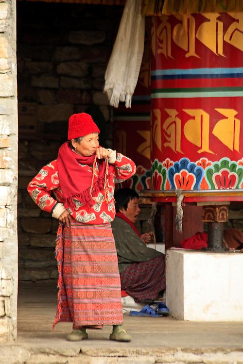 Asia, Bhutan, Thimpu. Woman standing at the prayer wheels of the Memorial Chorten in Thimpu, Bhutan.