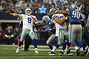 Dallas Cowboys quarterback Tony Romo (9) throws a pass as he gets pressured by Detroit Lions defensive end Ezekiel Ansah (94) during the NFL week 18 NFC Wild Card postseason football game against the Detroit Lions on Sunday, Jan. 4, 2015 in Arlington, Texas. The Cowboys won the game 24-20. ©Paul Anthony Spinelli