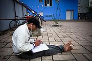 Un ragazzo Touareg ascolta musica e prende appunti. Cortile d'ingresso ex palazzine olimpiche.