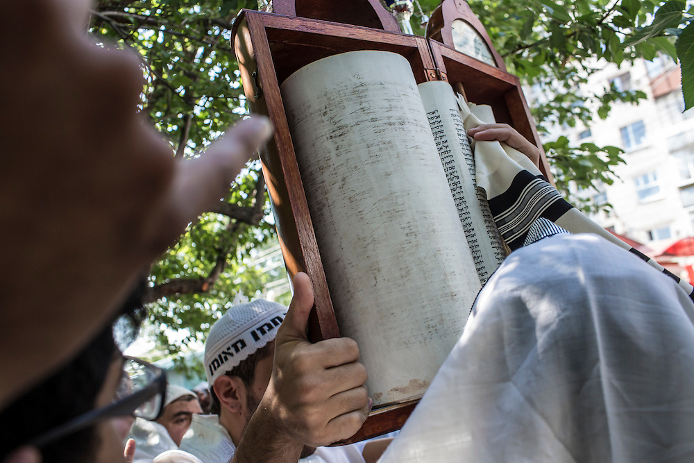 UMAN, UKRAINE - SEPTEMBER 14: Hasidic pilgrims hold a Torah scroll as they pray near the burial site of Rebbe Nachman of Breslov on September 14, 2015 in Uman, Ukraine. Every year, tens of thousands of Hasidim gather for Rosh Hashanah in the city to pray at the holy site. (Photo by Brendan Hoffman/Getty Images) *** Local Caption ***