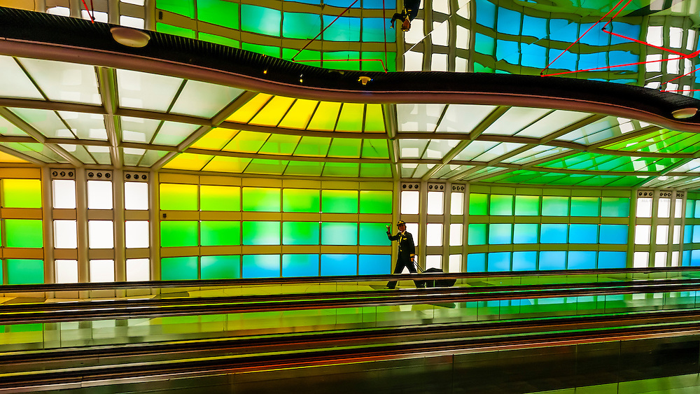 "A female airline pilot walks through the tunnel, passing ""Sky's the Limit"" by artist Michael Hayden at O'Hare International Airport, Chicago, Illinois USA."