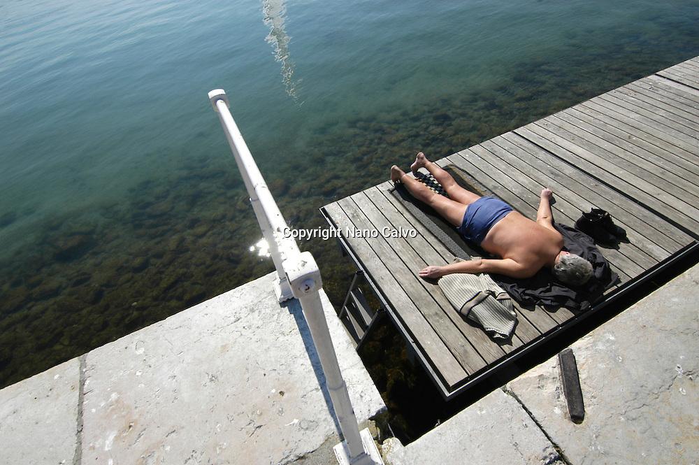An elderly man taking a sunbath in Bains des Paquis, in Geneva, Switzerland