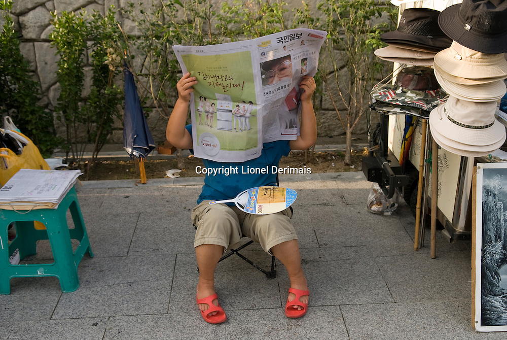 Korean woman reading a newspaper in Seoul, South Korea.