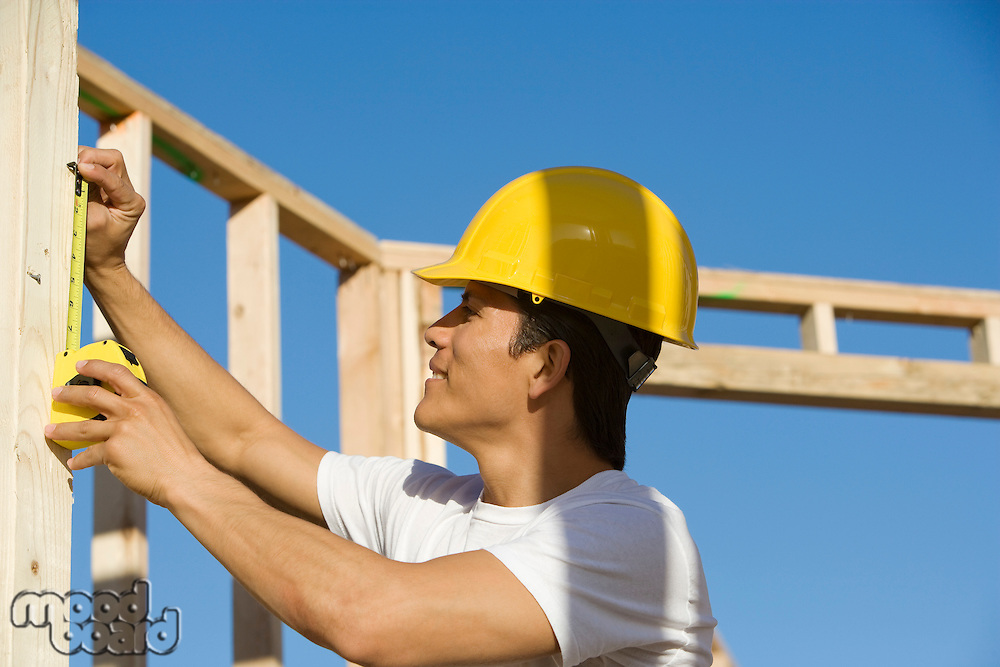 Construction worker measuring building construction