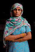 Nafeesa, 27, poses for a portrait without her 4 children aged 10, 7, 4, and 1.5 years, in her house compound in a slum in Tonk, Rajasthan, India, on 19th June 2012. Nafeesa's health deteriorated from bad birth spacing and over-working. While her husband works far from home, she rolls bidis (indian cigarettes) to make an income and support the family. She single-handedly runs the household and this has taken a toll on her health and financial insufficiencies has affected her children's health. Photo by Suzanne Lee for Save The Children UK