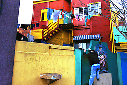 BUENOS AIRES, ARGENTINA:  A man climbs over a wall in a residental area of  La Boca in Buenos Aires, Argentina. The area of La Boca is known for it's European influence. .(Photo by Ami Vitale)
