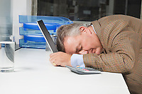 Side view of exhausted businessman with head on laptop in office