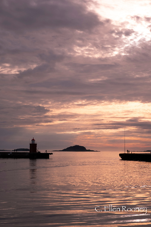 A dramatic sunset behind the lighthouse in the harbour in Alesund, More on Romsdal, Norway, Europe