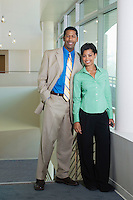 Business couple standing in office building, portrait