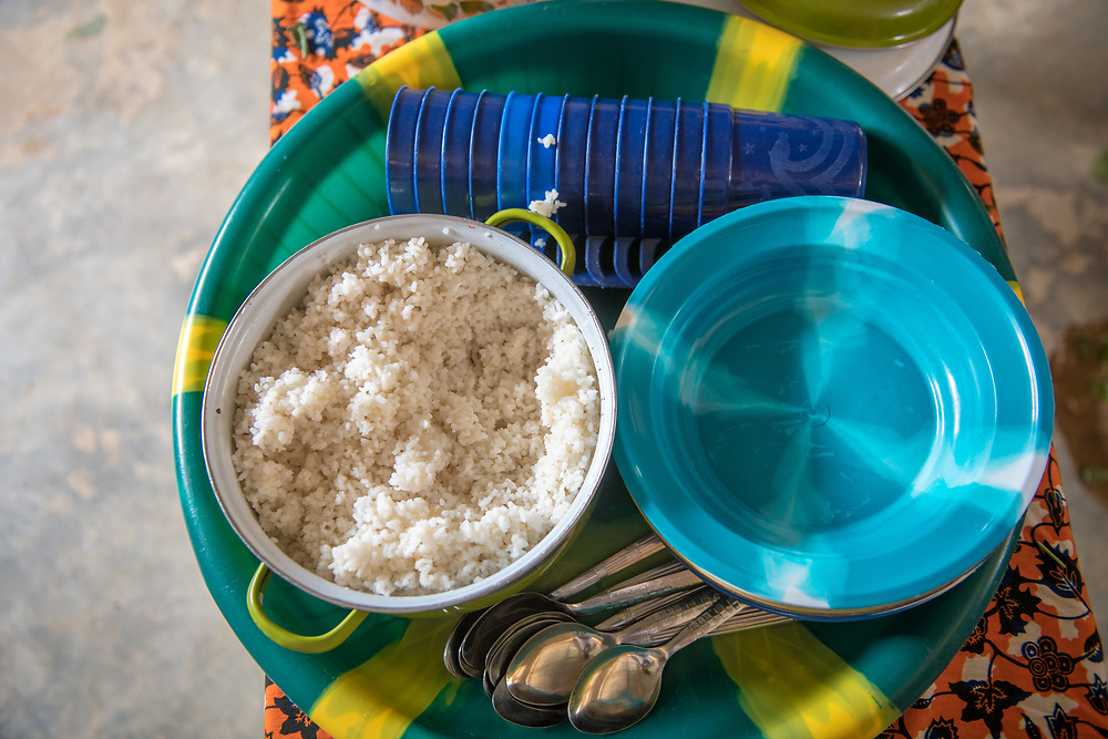 Rice(Oryza glaberrima, bowls, spoons, and cups all sit on a colorful tray in Ganta, Liberia