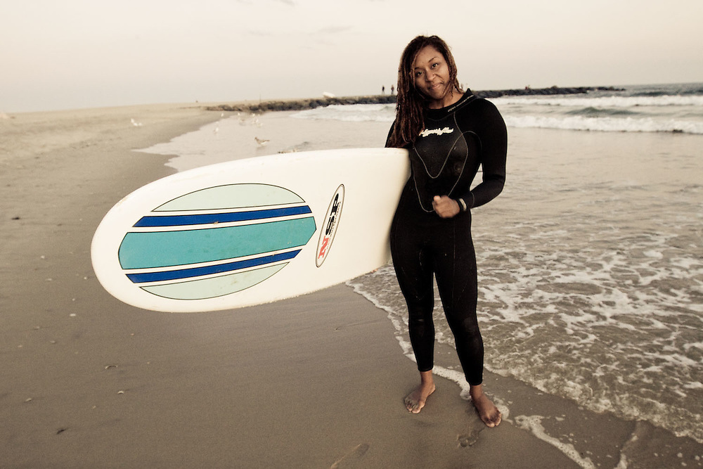 A female surfer poses with her surfboard, Rockaway Beach, Queens, NY.