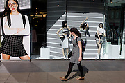 Woman shopper walks past stripe-themed shop window display.