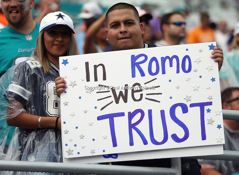 "A pair of Dallas Cowboys fans hold up a sign stating ""In Romo We Trust""  before the Dallas Cowboys 2015 week 11 regular season NFL football game against the Miami Dolphins on Sunday, Nov. 22, 2015 in Miami. The Cowboys won the game 24-14. (©Paul Anthony Spinelli)"