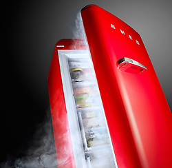 Shot of an open red Smeg freezer with cold vapour pouring out.