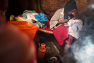 A woman breastfeeds here newborn children born the day her villages was bombed and she had to flee to nearby caves to live. Thousands of people have fled to caves to live after repeated bombing attacked by Sudan government forces on civilians areas.