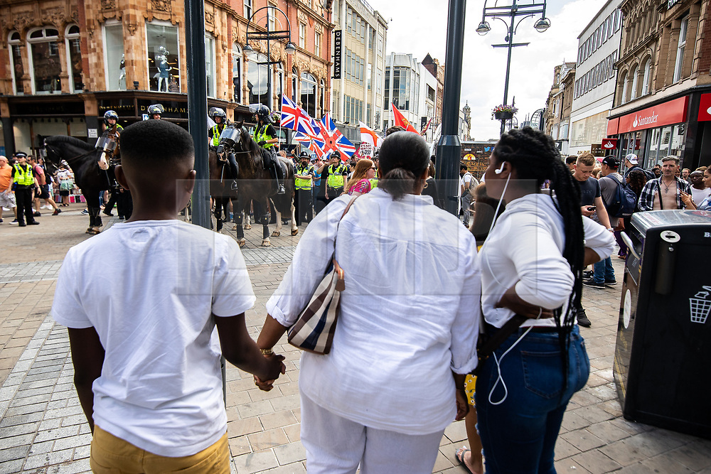 "© Licensed to London News Pictures . 07/07/2018 . Leeds , UK . A woman holds a boys hands and watches as an anti-Islam demonstration by supporters of jailed EDL founder Tommy Robinson , including those from the "" Yorkshire Patriots "" and "" First for Britain "" , passes through Leeds City Centre , opposed by anti-fascists . Robinson ( real name Stephen Yaxley-Lennon ) was convicted of Contempt of Court in May 2018 after committing a second offence , whilst serving a suspended sentence for the same crime . Photo credit : Joel Goodman/LNP"