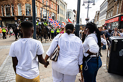 """© Licensed to London News Pictures . 07/07/2018 . Leeds , UK . A woman holds a boys hands and watches as an anti-Islam demonstration by supporters of jailed EDL founder Tommy Robinson , including those from the """" Yorkshire Patriots """" and """" First for Britain """" , passes through Leeds City Centre , opposed by anti-fascists . Robinson ( real name Stephen Yaxley-Lennon ) was convicted of Contempt of Court in May 2018 after committing a second offence , whilst serving a suspended sentence for the same crime . Photo credit : Joel Goodman/LNP"""