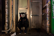 A man wearing a Kumamon mask rests during the Halloween celebrations Shibuya, Tokyo, Japan. Saturday October 27th 2018. The celebrations marking this event have grown in popularity in Japan recently. Enjoyed mostly by young adults who like to dress up, drink , dance and misbehave in parts of Tokyo like Shibuya and Roppongi. There has been a push back from Japanese society and the police to try to limit the bad behaviour.