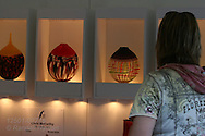 Woman admires display of blown-glass vases in artist's booth at St. Louis Art Fair, nationally renowned for attracting high-end works of art in all media; Clayton, Missouri.