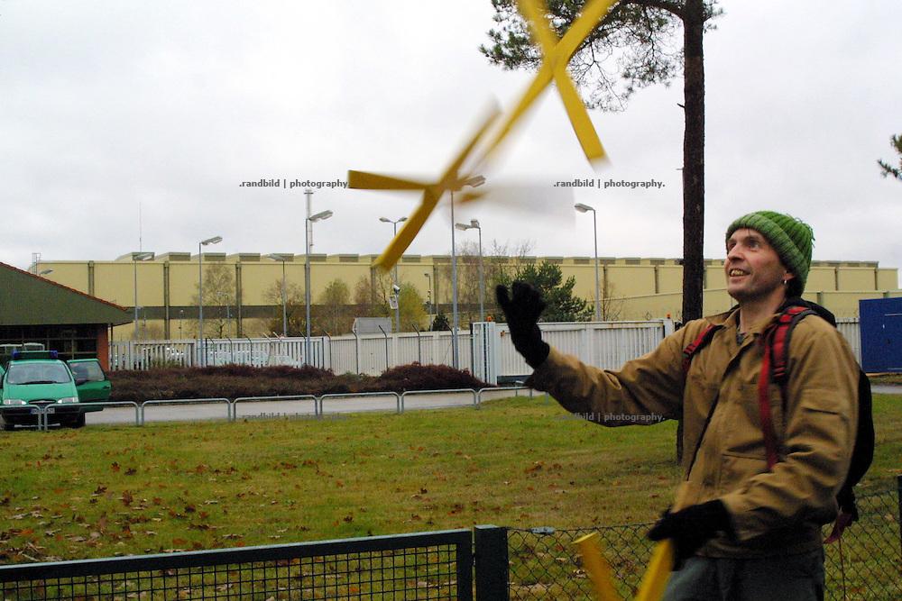 Ein Strassenkünstler jongliert vor der Castorhalle des Zwischenlager Gorleben (Hinten) mit gelben Xen. Das X ist das Symbol der Anti-Castor-Bewegung.