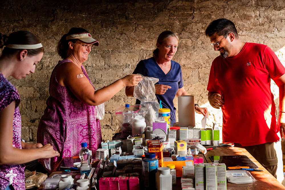 LCMS Missionaries Molly Christensen, Angie Thompson, Stephanie Schulte, and the Rev. Doug Thompson fill prescriptions in the pharmacy on the second day of the LCMS Mercy Medical Team on Tuesday, May 8, 2018, in the Yardu village outside Koidu, Sierra Leone, West Africa. LCMS Communications/Erik M. Lunsford
