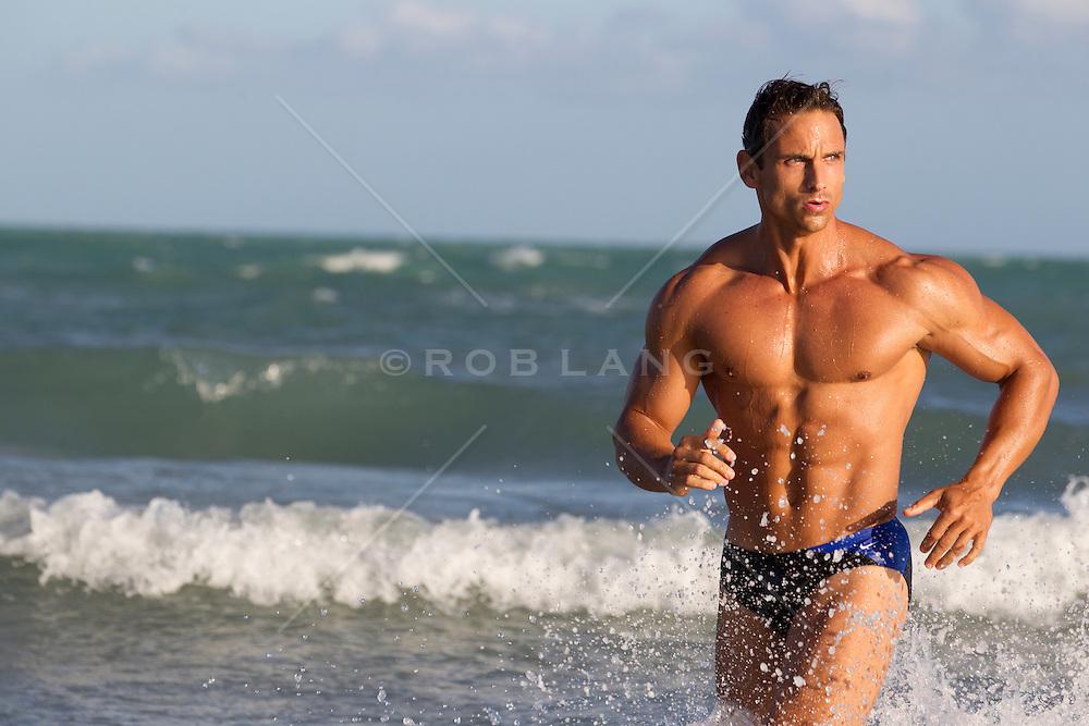 muscular man running in the ocean in Florida