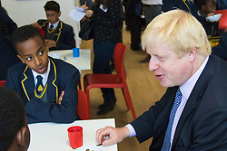 Michaela Community School, Wembley, London, June 23rd 2015. Mayor of London Boris Johnson visits the Michaela Community School, a Free School in Wembley that started taking students in September2014 after battling a certain amount of resistance from locals and unions. During the visit Head Teacher Katharine Birbalsingh took the Mayor on a tour of the school before he participated in a history lesson, prior to sitting down with pupils for brunch. PICTURED: Boris Johnson chats with pupils during brunch.