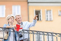 Happy man showing something to woman with guidebook in city