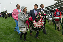Abel Tasman assistant trainer Jimmy Barnes and exercise rider Dana Barnes carry the garland of lilies off the track after winning the 143rd running of the Longines Kentucky Oaks at Churchill Downs May 5, 2017.