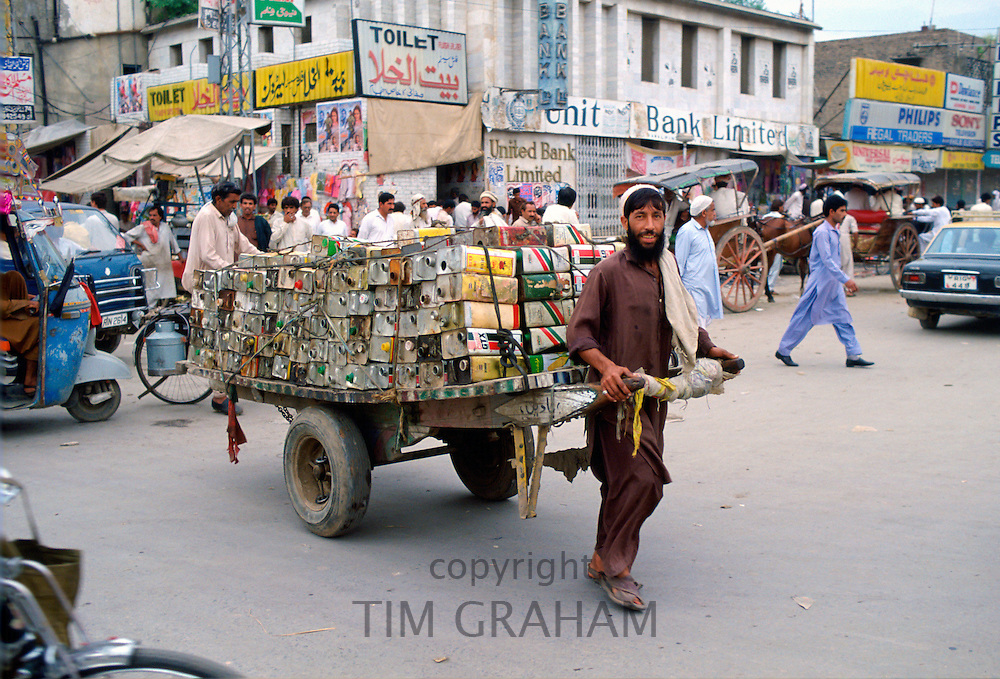 A man in Islamabad, Pakistan dragging a trailer loaded with empty oil cans through the crowded street.