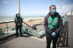 © Licensed to London News Pictures. 23/05/2020. Brighton, UK. Stewards stand at the entrance to the beach on the sea front at Brighton in West Sussex after local authorities became concerned with the number of people visiting the resort during days of sunny weather. The government has announced a series of measures to slowly ease lockdown, which was introduced to fight the spread of the COVID-19 strain of coronavirus. Photo credit: Peter Macdiarmid/LNP