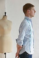 Tailor standing next to mannequin side view