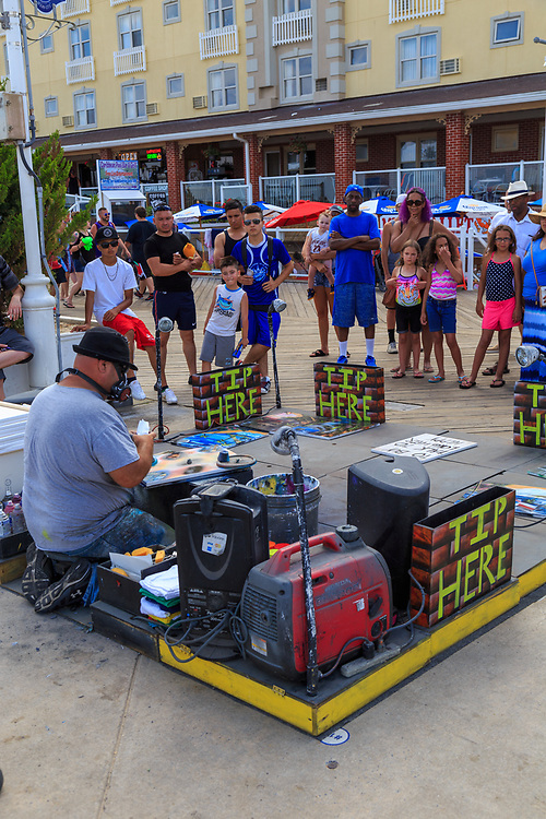 Ocean City, MD - July 10, 2016: As an artist works on the boardwalk, in Ocean City Maryland, a crowd gathers and watches