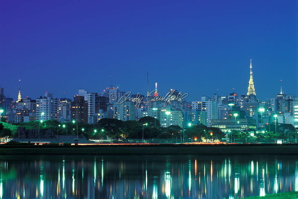Ibirapuera park at dusk, lights of this megacity reflected in Sunrise Lake. Communication towers of Paulista Avenue at .top of skyline. Sao Paulo, BRAZIL