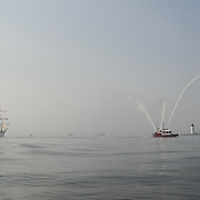 The City of Portsmouth Fire Boat escorts tall ship Gazela past Portsmouth Light and Fort Constitution on New Castle, as Gazela enters the Portsmouth, NH harbor.