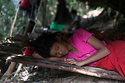 A young girl rests on her bed inside her families traditional shelter.<br /> <br /> Evidence suggests that the Maniq, a Negrito tribe of hunters and gatherers, have inhabited the Malay Peninsula for around 25,000 years. Today a population of approximately 350 maniq remain, marooned on a forest covered mountain range in Southern Thailand. Whilst some have left their traditional life forming small villages, the majority still live the way they have for millennia, moving around the forest following food sources. <br /> <br /> Quiet and reclusive they are little known even in Thailand itself but due to rapid deforestation they are finding it harder to survive on the forest alone and are slowly being forced to move to its peripheries closer to Thai communities.
