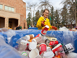 Savannah Phalan 15, tosses a cup into a recyclable bin while working on a table of trash during Garbology on Red Square, where grash from different locations is sorted to determine how much is recycleable or compostable at PLU on Tuesday, March 17, 2015. (Photo: John Froschauer/PLU)