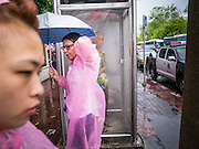 05 MAY 2013 - BANGKOK, THAILAND:  A tourist with an umbrella walks past a woman sheltering in a disused phone booth during an unseasonal thunderstorm near the Grand Palace in Bangkok, Thailand. The rainy season in Bangkok is usually mid June through early November, but 2013 has seen unseasonal rains through what is normally Bangkok's dry season.       PHOTO BY JACK KURTZ