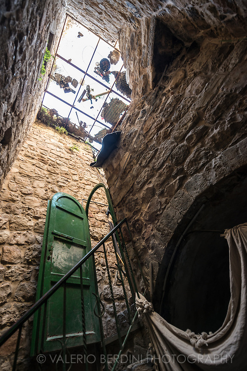 The courtyard of a building hosting some Palestinian homes in Hebron Old City. The roof has been protected with a wire fence. This barrier is put up to stop the garbage (visible on top) thrown by the Jewish settlers using the courtyard as a waste bin.
