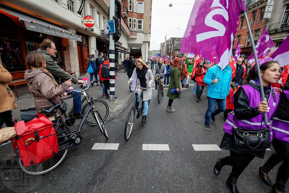 Fietsers wurmen zich langs de demonstranten. In Amsterdam wordt door de vakbond CNV samen met het FNV onder de noemer #naardedam een grote manifestatie gehouden voor een sociaal Nederland en tegen het beleid van de regering waarbij veel geld naar grote bedrijven en de aandeelhouders gaat in plaats van naar de bevolking. Er deden naar schatting tussen de vijf- en achtduizend demonstranten mee met de actie.<br /> <br /> In Amsterdam trade unions CNV and FNV held a big demonstration against the Dutch government. According to the unions too much money is going to big companies and their shareholders instead of to a social country.