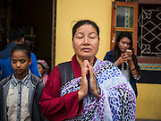 31 JULY 2015 - KATHMANDU, NEPAL: Tibetan Buddhist women pray at the entrance to the plaza around Bodhnath Stupa before joining the full moon procession around the Stupa. Bodhnath Stupa in the Bouda section of Kathmandu is one of the most revered and oldest Buddhist stupas in Nepal. The area has emerged as the center of the Tibetan refugee community in Kathmandu. On full moon nights thousands of Nepali and Tibetan Buddhists come to the stupa and participate in processions around the stupa. The stupa was heavily damaged in the earthquake of 25 April 2015 and people are no longer allowed to climb on the stupa, now they walk around the base and pray with butter lamps.   PHOTO BY JACK KURTZ