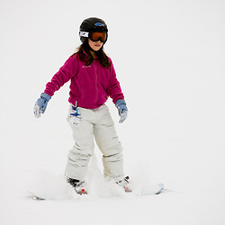 A girl (age 11) snowboarding at the Quechee Ski Hill in Quechee, Vermont.