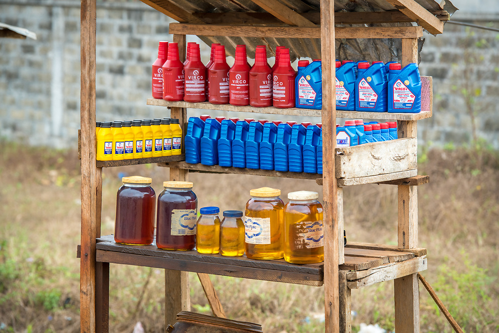 Colorful bottles of gasoline are neatly lined up on a wooden stand in Ganta, Liberia