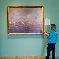 A journalist stands in front of one of the Francesco Guardi Paintings during the Press Preview at Museo Correr of the Guardi Exhibition From September 29th 2012 to January 6th 2013.In the third centenary of the birth of Francesco Guardi, the last great landscape artist of the 18th century, the monographic exhibition promoted by the Fondazione dei Musei Civici di Venezia aims to highlight his complex artistic production, from the lesser-known figure paintings of his youth to the 'interior scenes', concluding with the splendid views of Venice and his fabulous capriccios, painted in his maturity and old age.